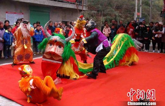 """现场头戴面具,扮演孙悟空、沙悟净的演员,跳起欢乐喜庆的傩舞""""斗牛狮""""。"""
